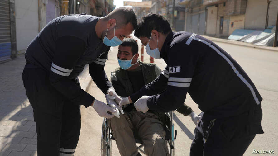 Health workers put gloves on a man in a wheelchair on an empty street, as restrictions are imposed to prevent the spread of the coronavirus in Qamishli, Syria, March 23, 2020.