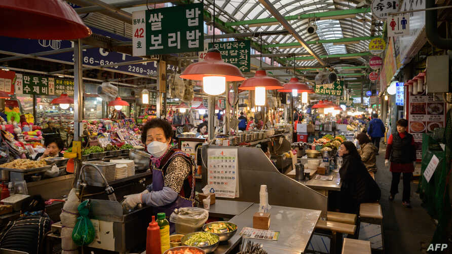 A vendor waits for customers at a market in Seoul on April 20, 2020. (Photo by Ed JONES / AFP)