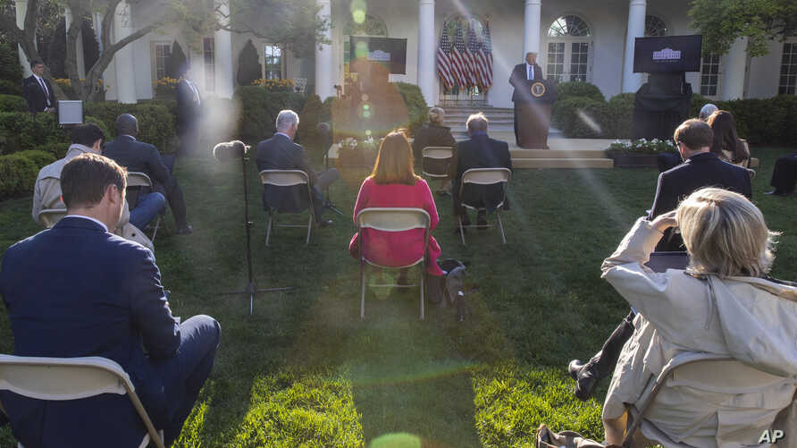 Reporters are seated a social distance apart as President Donald Trump speaks about the coronavirus in the Rose Garden of the White House, April 15, 2020, in Washington.