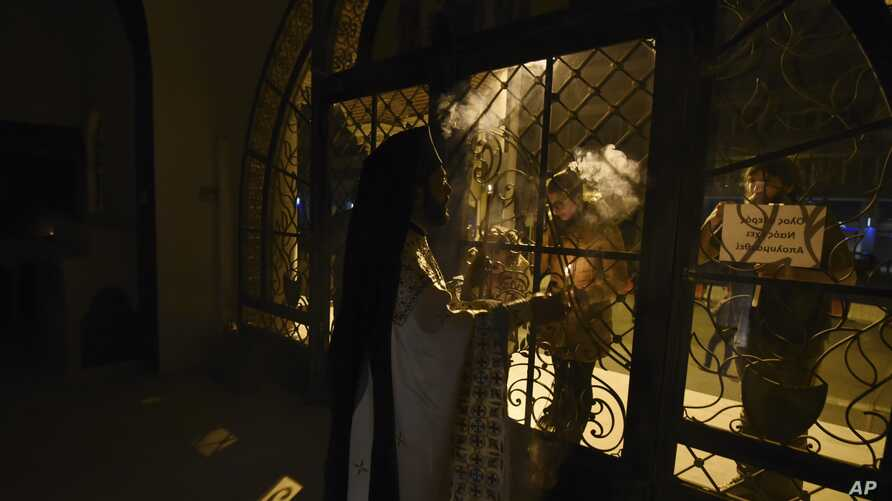 Faithful stand outside a closed for the public Greek Orthodox church as a priest takes part in the Good Saturday ceremony, in the northern city of Thessaloniki, Greece, during a lockdown order, April 19, 2020.