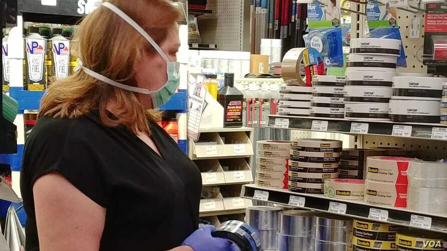 2--Customer Susan Buenaventura checks out painting supplies at Village Hardware in Alexandria, Virginia.(D. Block/VOA)