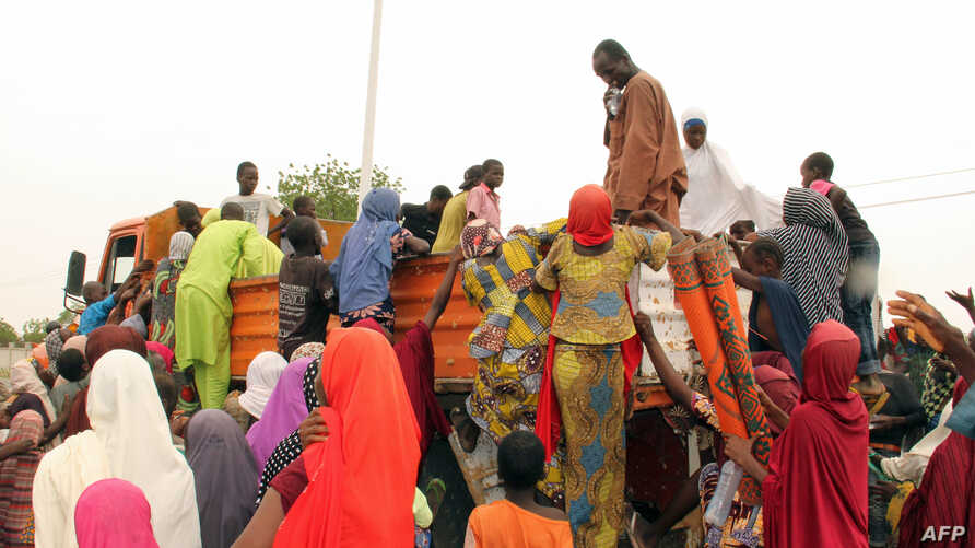 FILE - People, mostly women and children, internally displaced by Boko Haram militants, try to climb a truck protesting food shortages and a diversion of aid supplies meant for them, at a camp in Maiduguri, northeast Nigeria, on June 27, 2019.