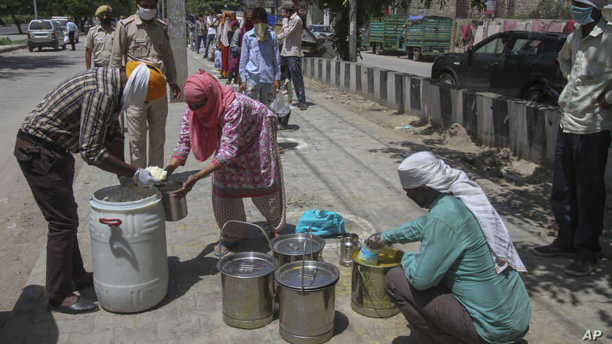 Volunteers distribute food to the poor during a lockdown to prevent the spread of the new coronavirus, in the Dwarka area of New Delhi, India, April 12, 2020.