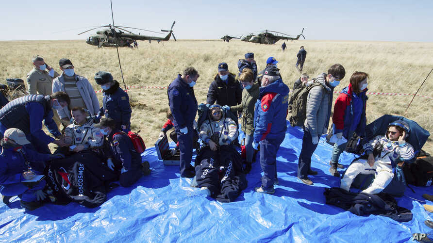 In this handout photo by the Roscosmos space agency, U.S. astronauts Andrew Morgan, left, Jessica Meir, right, and Russian cosmonaut Oleg Skripochka sit shortly after landing in a Soyuz MS-15 space capsule near Dzhezkazgan, Kazakhstan, April 17, 2020.