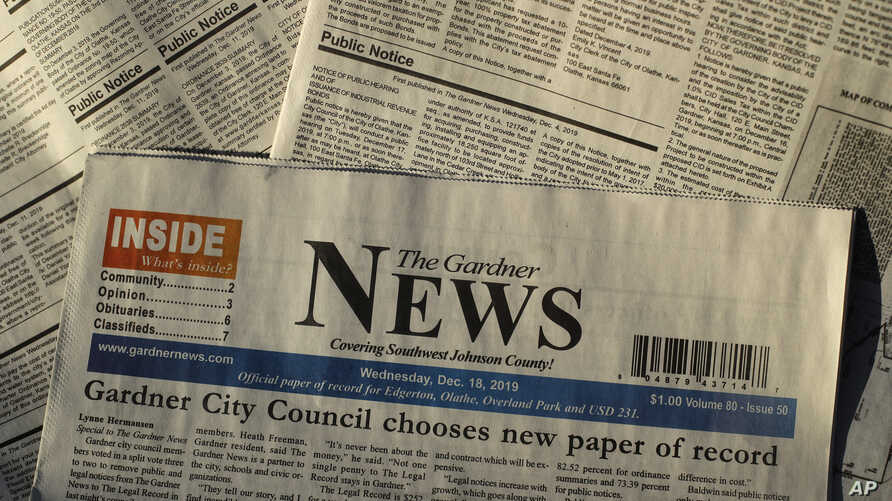 FILE - Pages of the The Gardner News are seen in an illustration photo in Gardner, Kansas, Dec. 20, 2019. A steep drop in advertising revenue has forced many local papers in the U.S. to make significants cuts or close altogether.