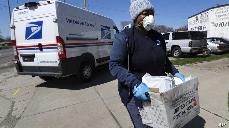 A United States postal worker outfitted with gloves and a mask makes a delivery in Warren, Michigan, April 2, 2020. The U.S. has suspended mail to 22 countries due to the COVID-19 pandemic.