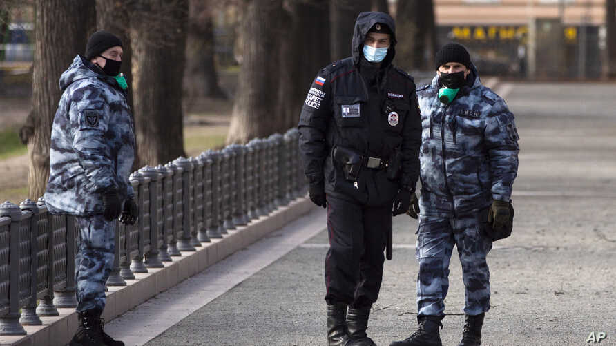 FILE - Police officers wearing face masks patrol at Patriarch Ponds in Moscow, Russia, April 22, 2020.