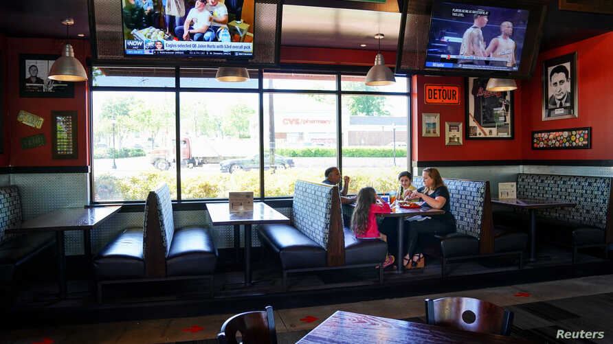 Laura Haque eats lunch with her family at Bad Daddy's Burger Bar on the day restaurants and theaters were allowed to reopen to the public in Smyrna, Georgia, April 27, 2020.