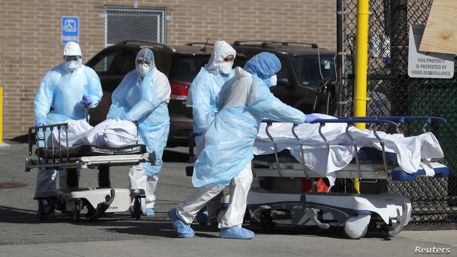 Healthcare workers wheel the bodies of deceased people outside the Wyckoff Heights Medical Center during the outbreak of the coronavirus disease (COVID-19) in the Brooklyn borough of New York City, April 6, 2020.