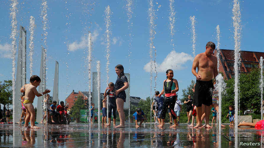 Kids and adults cool off in a fountain on the Rose Kennedy Greenway on the first day of a forecasted summer heatwave in Boston,…