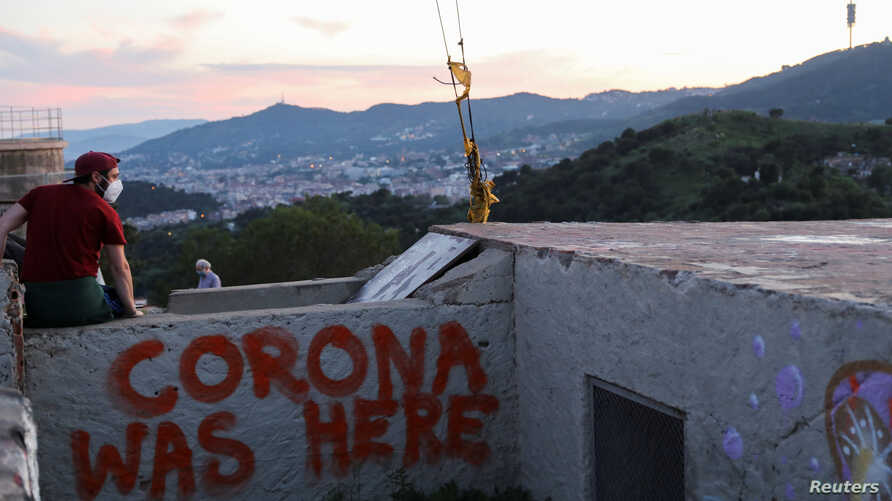 A man wears a protective face mask at a lookout point as a general view of the city of Barcelona is seen in the background