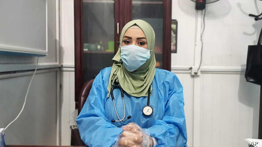 This May 13, 2020, picture provided by Dr. Marwa al-Khafaji shows the doctor back at work after 20 days in isolation
