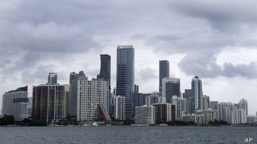 """Clouds loom over the Miami skyline Thursday, May 14, 2020. According to the National Hurricane Center website, """"A trough of low…"""