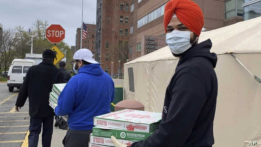Japneet Singh, right, delivers pizza to health care workers at Kings County Hospital