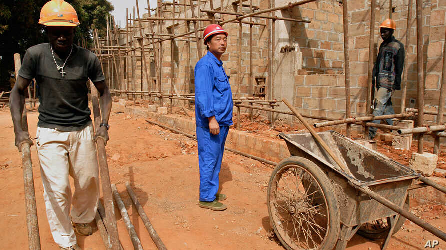 ** ADVANCE FOR MONDAY, SEPT. 3 ** A Chinese foreman looks on as laborers work on the construction of military officers housing,…