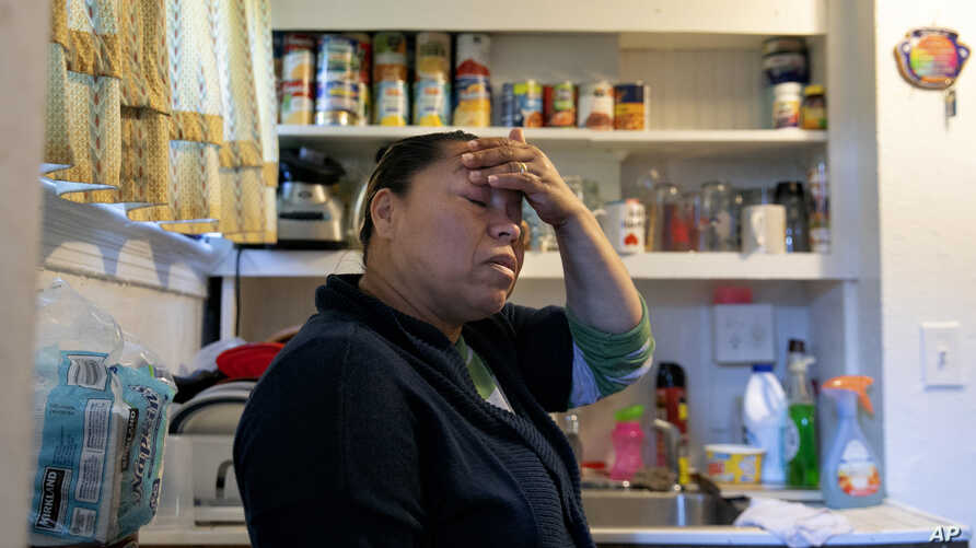 After cooking their one meal for the day of beans, egg, and handmade tortillas, Janeth worries while standing in her kitchen.