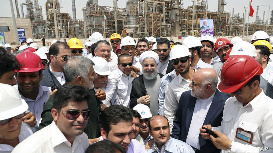 FILE - Iranian President Hassan Rouhani, center, inaugurates the Persian Gulf Star Refinery in Bandar Abbas, Iran, April 30, 2017.