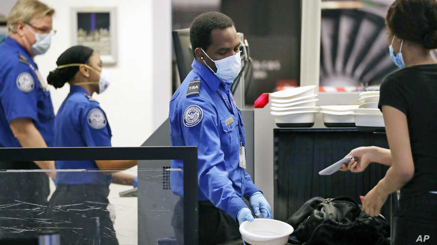 TSA officers wear protective masks at a security screening area at Seattle-Tacoma International Airport Monday, May 18, 2020,…