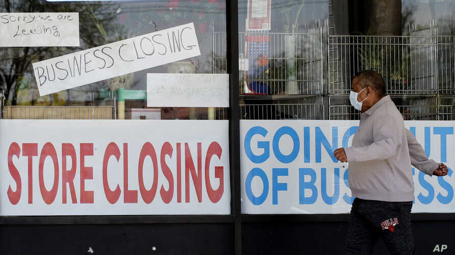 A man looks at signs of a closed store due to COVID-19 in Niles, Ill., Thursday, May 21, 2020. More than 2.4 million people…