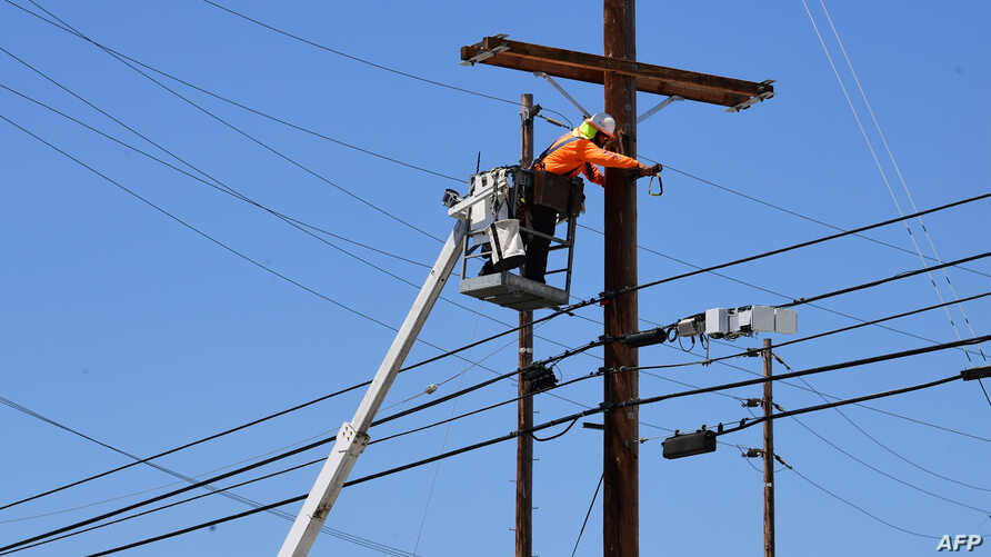 FILE - A man works on power lines in Los Angeles, California, May 4, 2020.