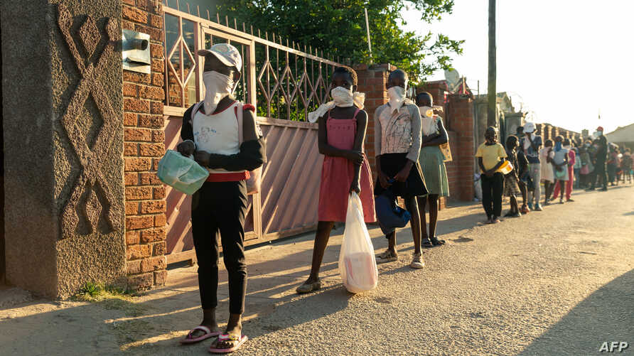 FILE - People line up for a food handout amid the coronavirus pandemic, in Chitungwizaon, Zimbabwe, May 5, 2020.