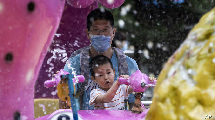 A man wearing a mask to curb the spread of the new coronavirus and a child, who temporarily removed his, enjoy a ride at a local park in Beijing, China, May 23, 2020.