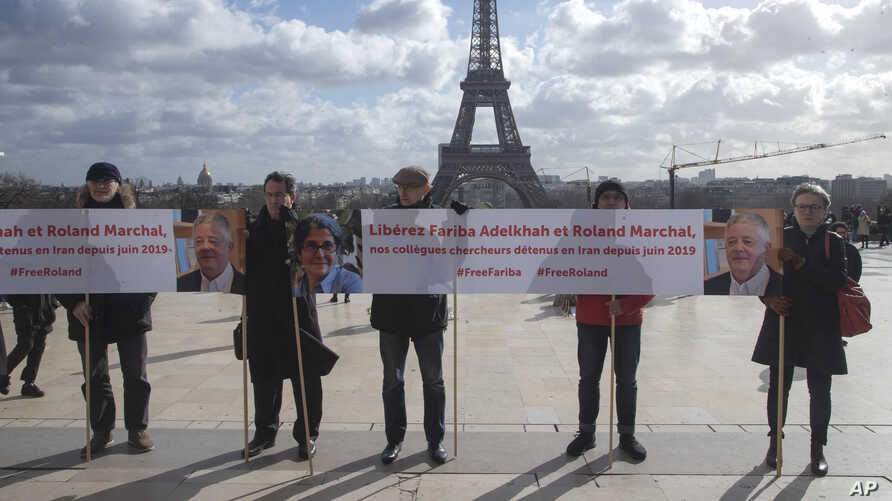 FILE - Activists holding banners at Trocadero square in Paris, France, Feb. 11, 2020, call for the release of scientists Fariba Adelkhah and Roland Marchal, both imprisoned in Iran.