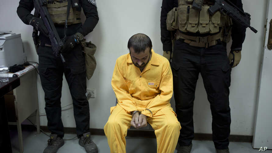 FILE - Abu Hareth, an Iraqi Islamic State preacher who owned Yazidi slaves, is seen under guard by Iraqi special forces before an interview, in Baghdad, Iraq, Aug. 28, 2019.