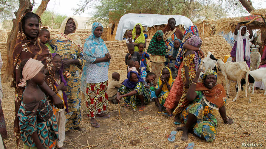 FILE - Nigerian refugees, who fled into Niger following attacks on their village, stand in the yard of their Nigerien host, in Diffa, southeastern Niger, June 21, 2016.