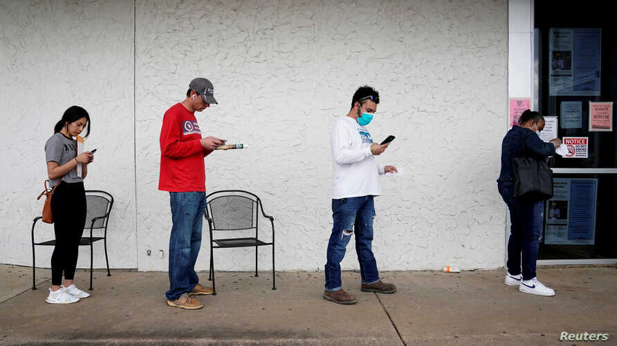 FILE - People who lost their jobs wait in line to file for unemployment at a Workforce Center in Fayetteville, Arkansas, April 6, 2020.