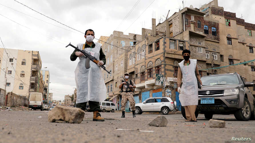 FILE - Security officers wearing protective masks stand on a street during a 24-hour curfew amid concerns about the spread of the coronavirus, in Sanaa, Yemen, May 6, 2020.