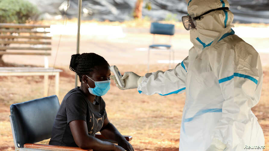 FILE - A woman has her temperature checked by a health care worker during a nationwide lockdown to help curb the spread of the coronavirus, at a screening center in Harare, Zimbabwe, April 30, 2020.
