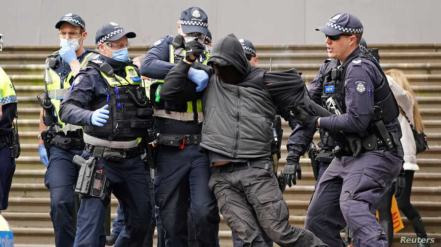 Police officers detain a protester opposing lockdown measures implemented to curb the spread of the coronavirus disease (COVID-19) outside Parliament House in Melbourne, Australia.