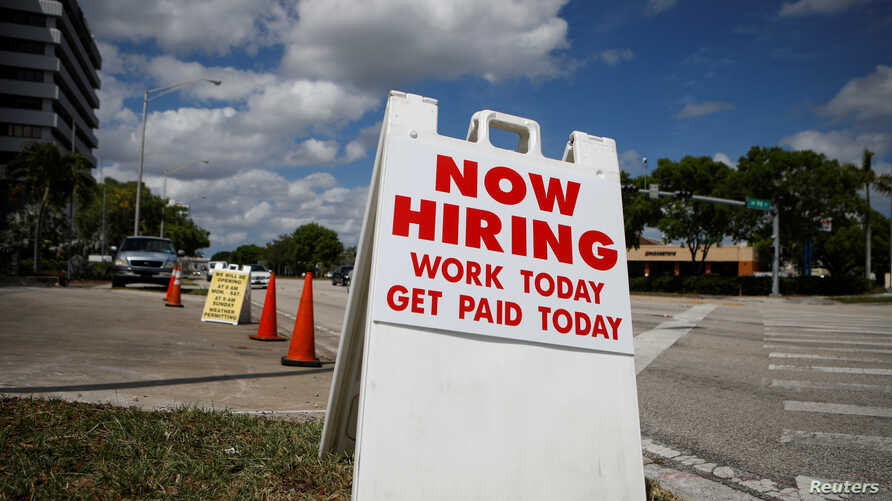 """A """"Now Hiring"""" sign advertising jobs at a hand car wash is seen along a street, as the spread of the coronavirus disease (COVID-19) continues, in Miami, Florida, May 8, 2020."""