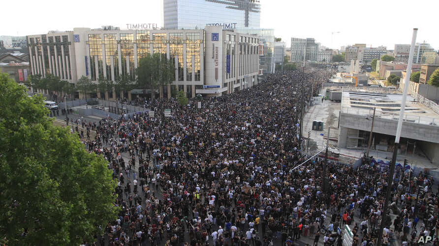 Protesters gather Tuesday, June 2, 2020 in Paris. Thousands of people defied a police ban and converged on the main Paris courthouse for a demonstration to show solidarity with U.S. protesters and denounce the death of a black man in French police custody.
