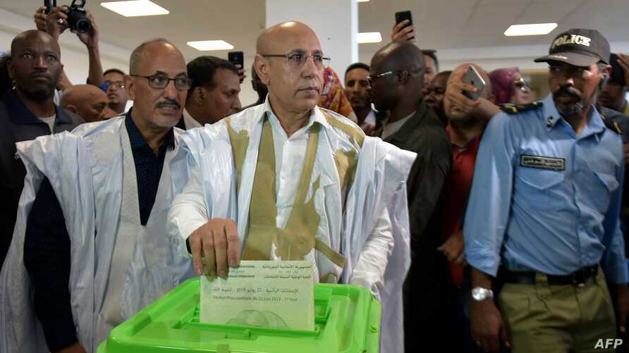 Presidential candidate Mohamed Ould Ghazouani (C) casts his ballot at a polling station on June 22, 2019 in Nouakchott during the presidential election in Mauritania.  Voters in the West African state of Mauritania went to the polls on June 22 after…