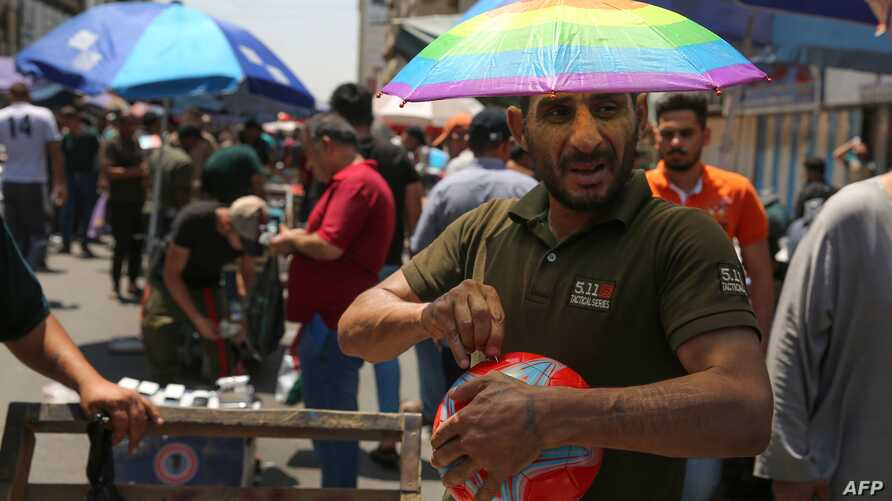 An Iraqi street vendor wears an umbrella-shaped hat to protect his head from the sun during a heat wave in the capital Baghdad, June 14, 2019.