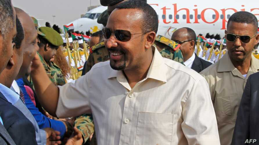 Ethiopia's Prime Minister Abiy Ahmed (C) is welcomed at Khartoum international airport on June 7, 2019. Ethiopia's prime minister arrived in Khartoum today seeking to broker talks between the ruling generals and protesters as heavily armed…