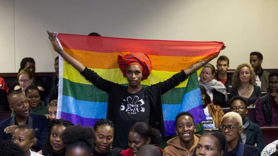 An activist holds up a rainbow flag to celebrate inside Botswana High Court in Gaborone on June 11, 2019. Botswana's Court ruled on June 11 in favour of decriminalising homosexuality, handing down a landmark verdict greeted with joy by gay rights…