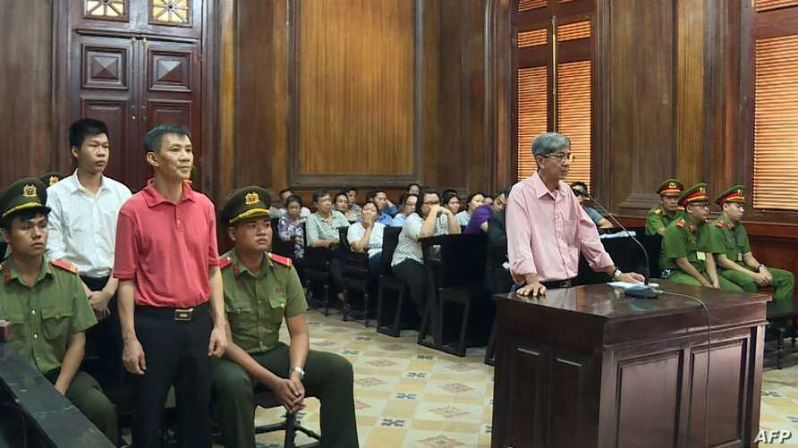 This picture from the Vietnam News Agency taken and released on June 24, 2019 shows US citizen Michael Nguyen (3rd L in red) standing on trial with other defendants in Ho Chi Minh City.  A Ho Chi Minh City court on June 24 jailed Nguyen for 12 years…