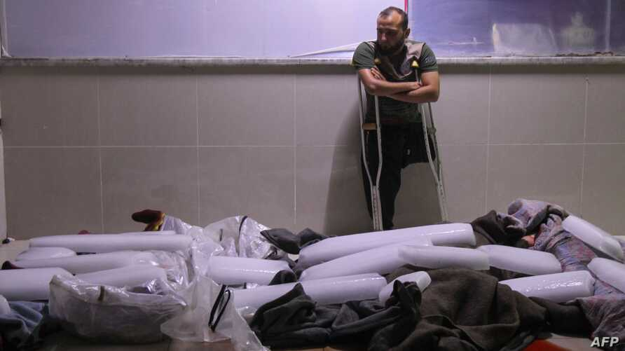 A Syrian amputee looks at bodies of civilians reportedly killed in regime airstrikes on the town of Muhambal, in the northern Idlib province, July 6, 2019.