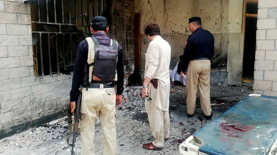 Pakistani security officials examine the site of a suicide bomb attack at the entrance of a hospital in Kotlan Saidan village on the outskirts of the northwestern city of Dera Ismail Khan on July 21, 2019. A female suicide bomber killed six people -…