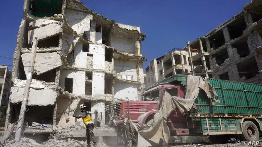 A member of the Syrian Civil Defense, also known as the White Helmets, stands in front of a heavily damaged building following an airstrike by regime forces in the rebel-held city of Idlib in northwestern Syria, July 12, 2019.