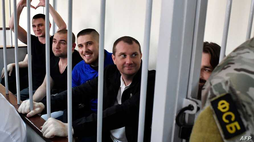 Ukrainian sailors sit inside a defendants' cage prior to a hearing at a court in Moscow on July 17, 2019.