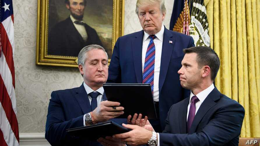 US President Donald Trump (C) watches as Guatemala's Interior Minister Enrique Degenhart (L) and Acting US Secretary of Homeland Security Kevin K. McAleenan (R) exchange documents while signing a safe-third agreement, regarding people seeking asylum…