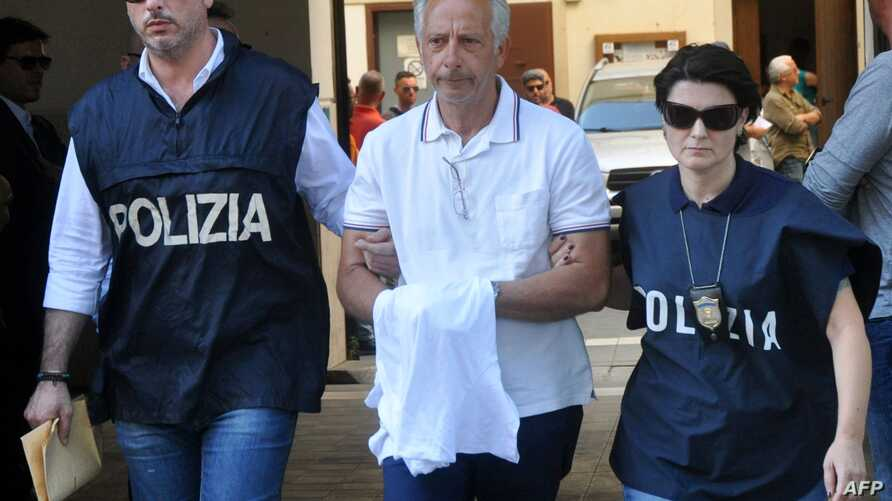 Italian police officers escort Francesco Inzerillo (C) after he was arrested in Palermo during an police/FBI operation called 'New Connection' on July 17, 2019. Italian anti-mafia police and the FBI in New York have arrested 19 people in a…