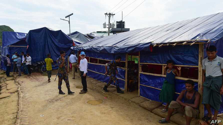 Officials of U.N. and Bangladesh police stand guard in front of a place where U.N. and refugee commission interviewed Rohingya families at a refugee camp in Teknaf, Aug. 21, 2019. Rohingya refugees said they did not want to return to Myanmar.