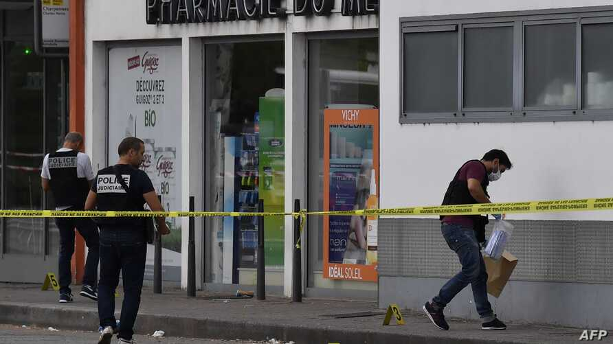 Police officers look for evidence in front of a pharmacy in Villeurbanne on the outskirts of Lyon, south-eastern France on August 31, 2019, after a knife attack which has left one dead and six injured.  Two men, one armed with a knife and the other…