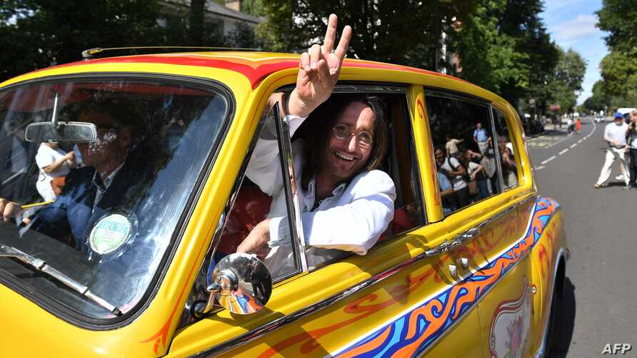 Beatles lookalike band 'Fab Gear' member John Lennon waves from his replica psychedelic rolls royce after joining fans at the famous Abbey Road zebra crossing in London, England on August 8, 2019, on the 50th anniversary of the day that the iconic…