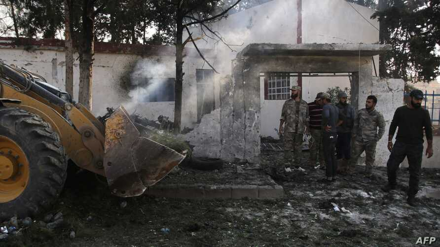 People gather at the site of a car bomb explosion in front the offices of a Turkey-backed group in the northern Syrian Kurdish…